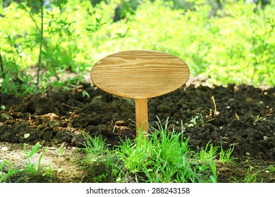 Wooden signboard over grass, outdoors