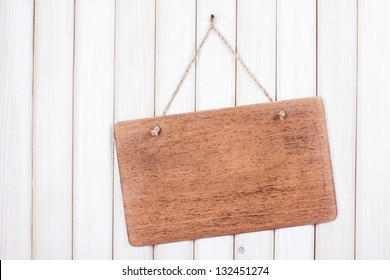 Wooden signboard with rope hanging on white wood planks background