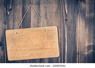 Wooden signboard with rope hanging on wood planks background