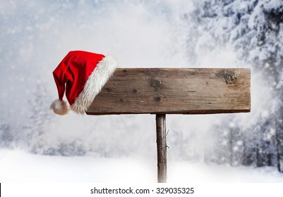 Wooden signboard with Santa's hat in snowy winter landscape
