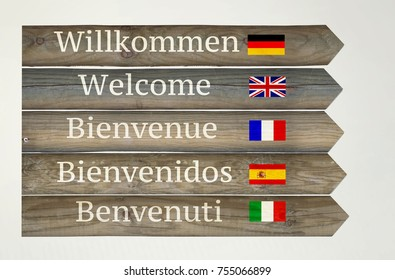 Wooden signboard showing welcome in five different languages with their flags and indications on light grey background