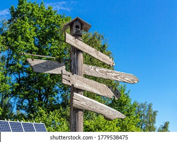 Wooden signpost with wooden arrows in the city Park, against the background of green trees, blue sky and solar panel