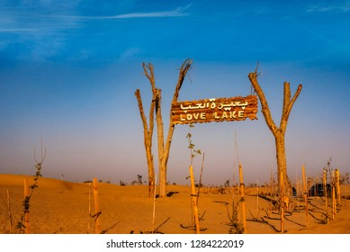 A wooden signpost at the entrance of Love Lake Dubai welcoming visitors. Love Lake Dubai is the new tourist destination in Dubai.