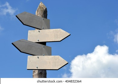 Wooden signpost with four arrows - great to type some information on it (copy space).