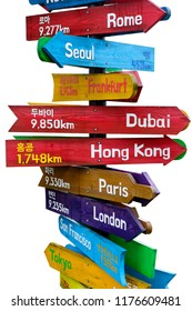 Wooden signpost indicating directions of nine world continents over white background with Korean text