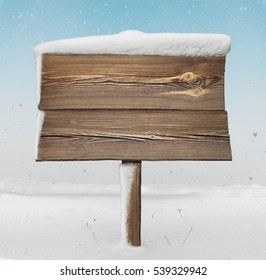 Wooden signpost with less snow on it and snowfall on background