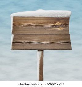 Wooden signpost with less snow on it and snow background