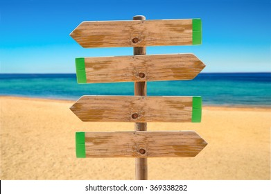 wooden signpost in the meadow with copyspace on the beach