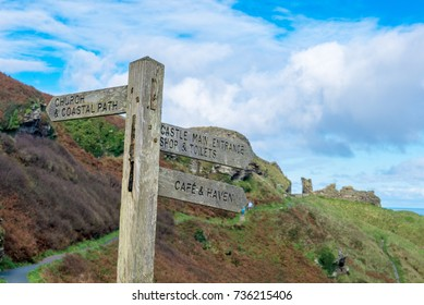 Wooden signpost pointing to a coastal path, castle and cafe