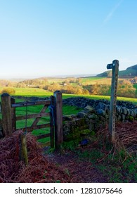 Wooden signpost points through a gate and over a meadow in the Derbyshire Peak District.