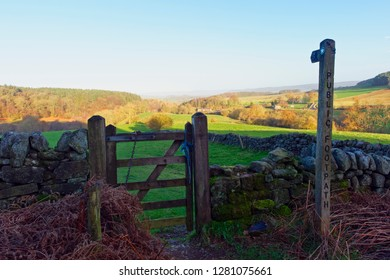 Wooden signpost points through a gate and over a shaded meadow in the Derbyshire Peak District.