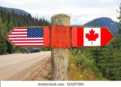 Wooden signpost with two arrows - american and canadian national flags on the highway road with nature landscape in the background. Canada and America moving direction sign
