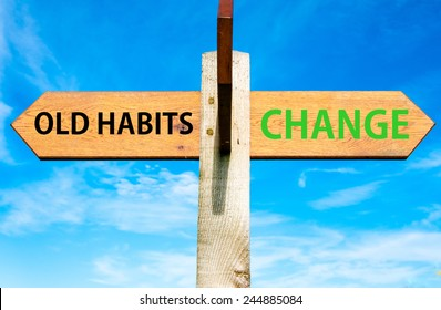 Wooden signpost with two opposite arrows over clear blue sky, Old Habits versus Change messages, Lifestyle change conceptual image