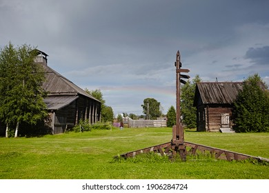 Wooden signpost in the village against the background of green grass and houses