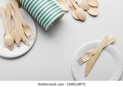 Wooden single use kitchenware and paper cups and plates on white. Top view