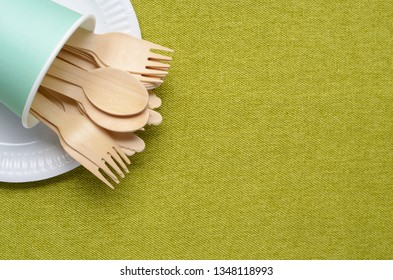 Wooden single use kitchenware in paper cup on table. Top view, space for text.