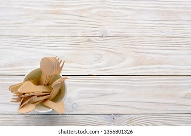 Wooden single use kitchenware in paper cup on white table. Top view, space for text.