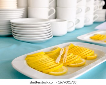 Wooden skewers lie on a stack of thin slices of lemon laid out in a stack. In the background are stacks of white ceramic cups and saucers. Tea party in Russian. The atmosphere in the restaurant.