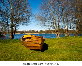 A wooden skiff placed on land next to the lake, waiting for the summer to come