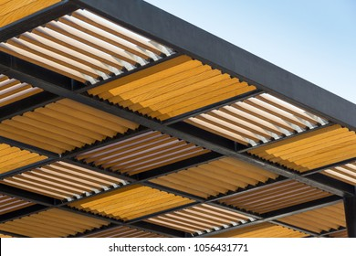 wooden slat shading with steel roof structure against blue sky, timber awning background.