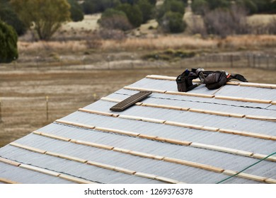 Wooden slats laying on rooftop with tool belt and clay tile in preparation for roofing
