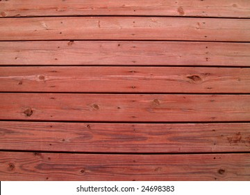 Wooden slats on a weathered wooden deck with redwood stain.