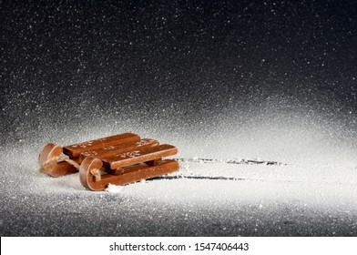 wooden sled toy in the snow, trail in the snow from the sled, white snow on a black background