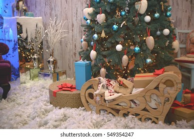 Wooden sleigh with gifts near a Christmas tree.