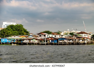 Wooden slums on stilts on the riverside of Chao Praya River in Bangkok, Thailand