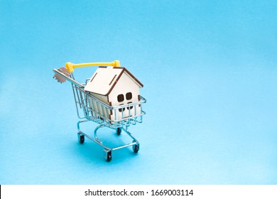 wooden small decorative house and a key to the lock in a shopping trolley, light blue background, copy space, sale and purchase of real estate concept
