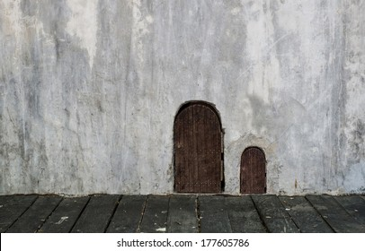wooden small door and bigger door on concrete grungy wall with wooden floor