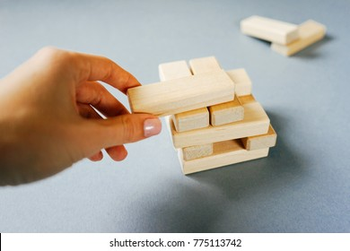 wooden small plaques, tabletop home game, someone's hand puts the plaques on each other