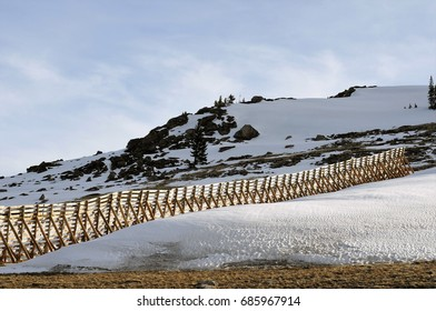 Wooden snow-drift fence runs up isolated hillside in the Big Horn Area, Montana