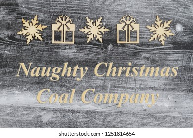 Wooden snowflake and Christmas presents on a weathered wood with Christmas message of Naughty Christmas Coal Company