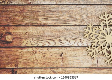 Wooden snowflake on a weathered wood background that you can use as a mock up for your message for the winter