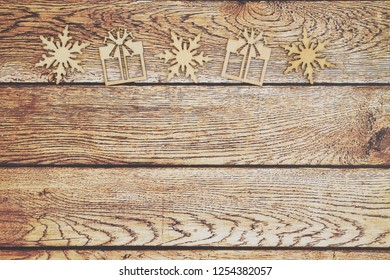 Wooden snowflakes and Christmas presents on a weathered wood background that you can use as a mock up for your message for Christmas