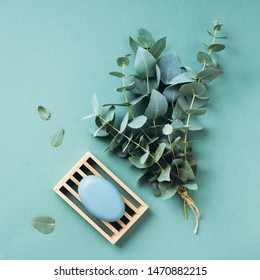 Wooden soap dish, soap, eucalyptus over green background. Zero waste, natural organic bathroom tools. Plastic free life. Ecological skin care, body treatment concept.
