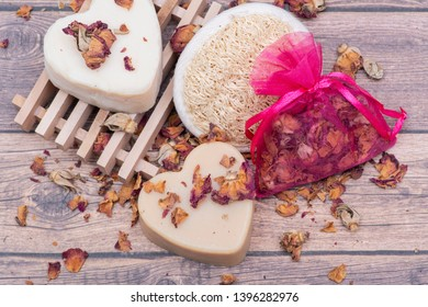 Wooden Soap Holder with a Heart shaped Goat milk Soap, Natural loofah sponge and dried roses on wooden background.