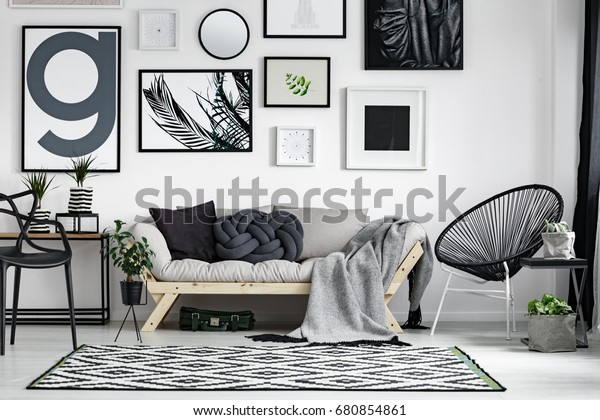 Wooden sofa with dark pillows in scandi style living room