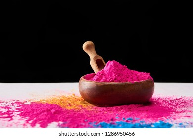 wooden spatula and bowl with pink holi powder on white table isolated on black