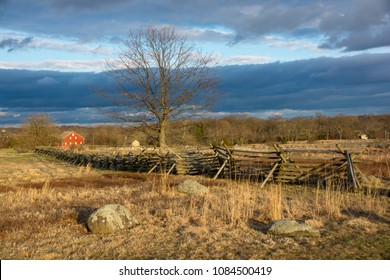 A wooden split rail fence and red barn stand lonely in a field in Gettysburg National Battlefield in Gettysburg, Pennsylvania, home to one of the bloodiest battles in the American Civil War.