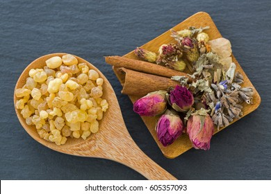 Wooden spoon of aromatic yellow resin gum next to dried flowers rose lavender cinnamon. Incense from Sudanese Frankincense tree made by slashing Boswellia sacra bark in Etiopia (Boswellia Papyrifera)