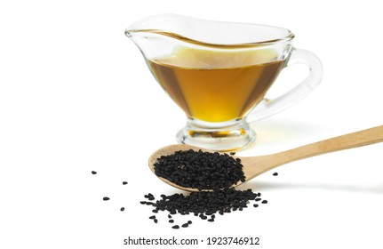 Wooden spoon with black cumin seeds and black seed oil Isolated on white background. Selective focus.