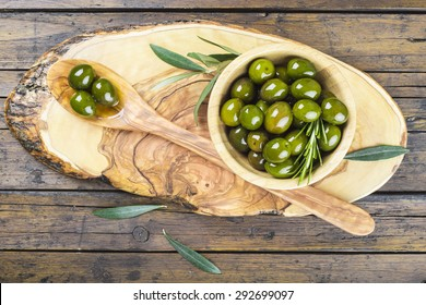 Wooden spoon and bowl with green olives on a cutting board on the table of the kitchen