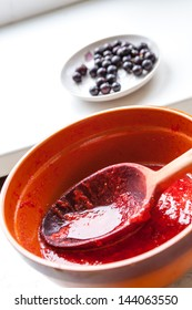 Wooden spoon in a bowl of jam with berries in background