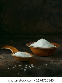 A wooden spoon and bowl of salt crystals on a dark low light  background with copy space for your text