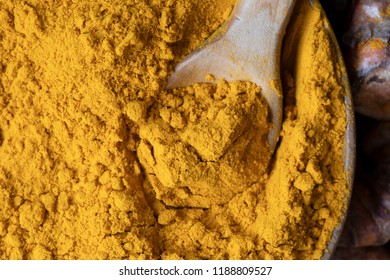 Wooden spoon in bowl of turmeric close up flat lay