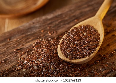 Wooden spoon with flax seeds on rustic background, top view, close-up, shallow depth of field, selective focus