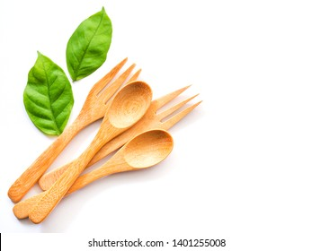 Wooden spoon and fork and green leaves, Natural wooden utensils Eco-friendly And safe for health With copy space for text of design.