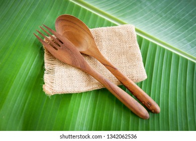 Wooden spoon and fork kitchenware set on sack banana leaf background / Zero waste use less plastic concept